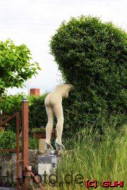 Nackte Frau beim Heckeschneiden